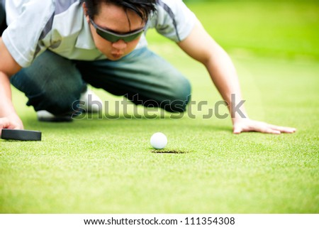 Golf player cheating blowing to get the ball into the hole - stock photo