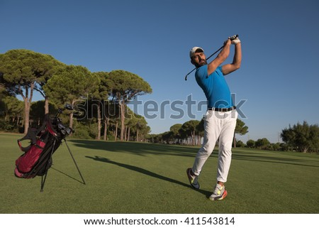 golf player hitting shot with club on course at beautiful morning with sun flare in background - stock photo