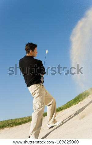 Golf player hitting the ball - stock photo