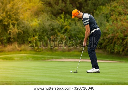 Golf player holding club, ready to hit ball - stock photo