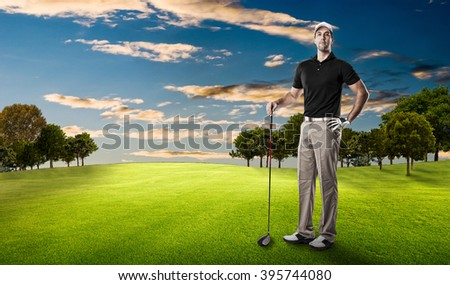 Golf Player in a black shirt standing on a golf course.