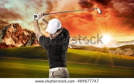 Golf Player in a black shirt taking a swing, on a golf course.