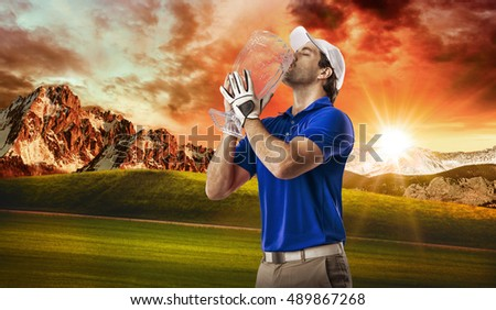 Golf Player in a blue shirt celebrating with a glass trophy in his hands, on a golf course.