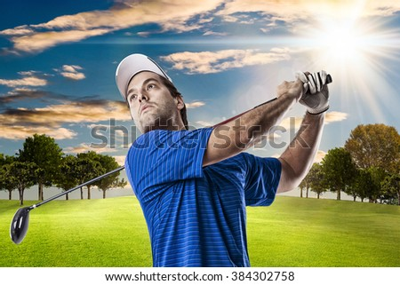 Golf Player in a blue shirt taking a swing, on a golf course.