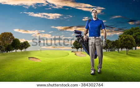 Golf Player in a blue shirt walking with a bag of golf clubs on his back, on a golf course.