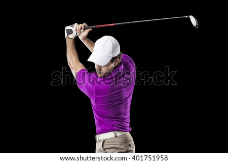 Golf Player in a pink shirt taking a swing, on a black Background. - stock photo