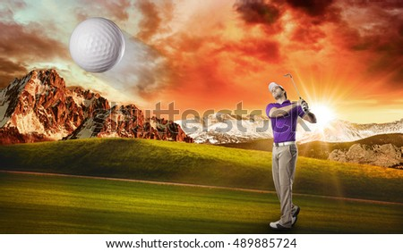 Golf Player in a purple shirt taking a swing, on a golf course.