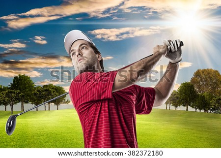 Golf Player in a red shirt taking a swing, on a golf course.