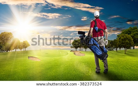 Golf Player in a red shirt walking with a bag of golf clubs on his back, on a golf course.