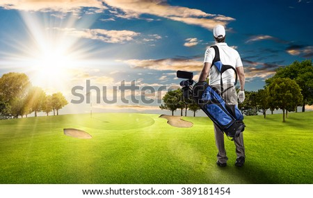 Golf Player in a white shirt walking with a bag of golf clubs on his back, on a golf course.