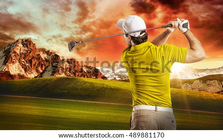 Golf Player in a yellow shirt taking a swing, on a golf course.