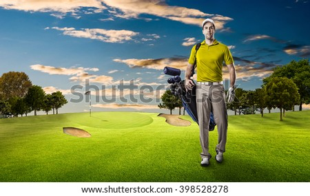 Golf Player in a yellow shirt walking with a bag of golf clubs on his back, on a golf course. - stock photo