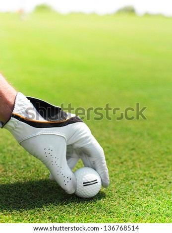 Golf player man holding golf ball in his hand - stock photo