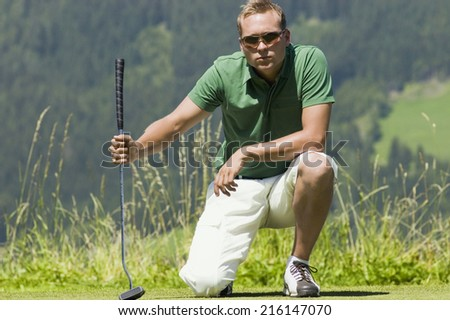 Golf player on golf course, squatting - stock photo