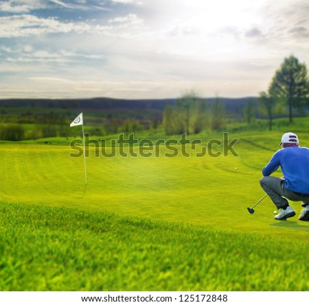 Golf player on the putting green aiming for putt - stock photo