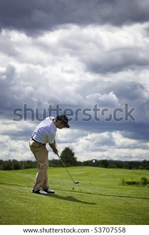 Golf player pitching the golf ball, ball in the air. - stock photo