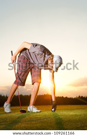 Golf player preparing a golf ball while sunset