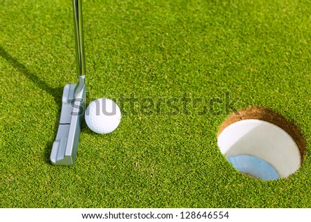 Golf player putting ball into hole, only ball, hole and iron to be seen - stock photo