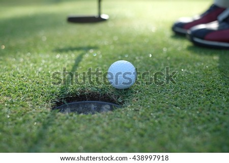 Golf player putting ball into hole, only feet and iron to be seen - stock photo