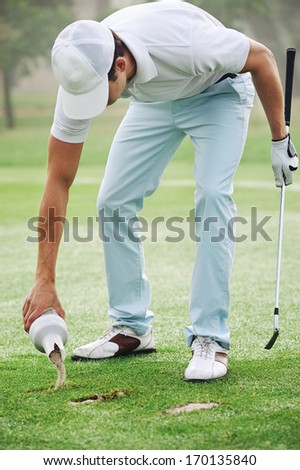 Golf player repairing divot with sand on fairway