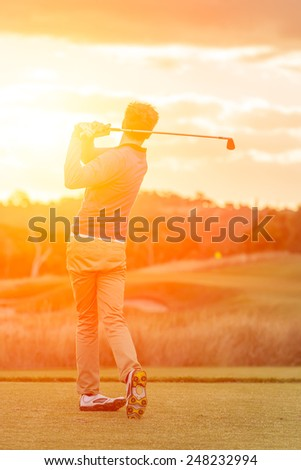 Golf player tee off at sunset with fairway and green in view. - stock photo