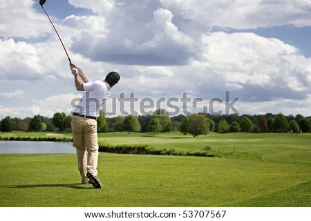 Golf player teeing off golf ball from tee box, wonderful cloud formation in background. - stock photo
