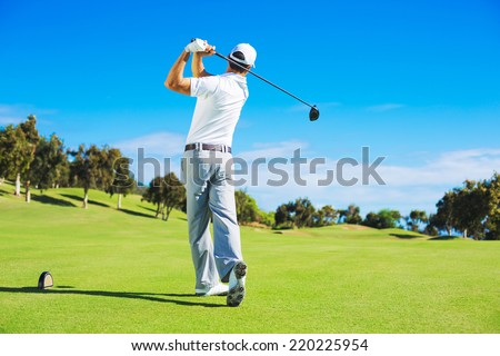 Golf player teeing off. Man hitting golf ball from tee box with driver. - stock photo