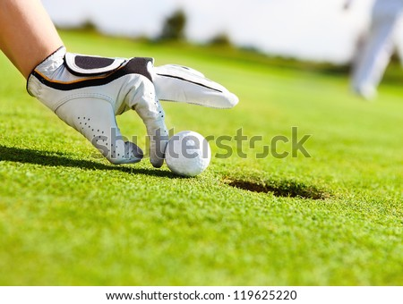 Golf player woman pushing golf ball into the hole - stock photo