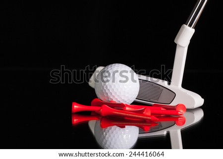 Golf putter and different golf equipments on the black glass desk