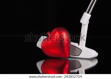 Golf putter and red heart on the black glass desk - stock photo