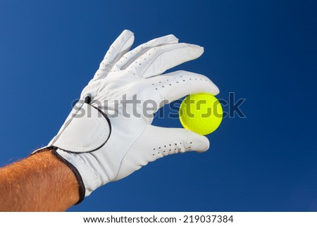 Golf: putter club with white golf ball on putting green - stock photo