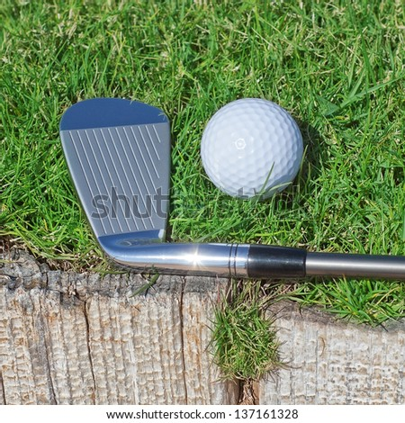 Golf stick and ball support wooden close-up on the grass. - stock photo