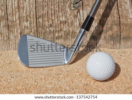 Golf stick and ball support wooden close-up on the sand. - stock photo