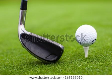 Golf tee ball club driver in green grass course closeup - stock photo