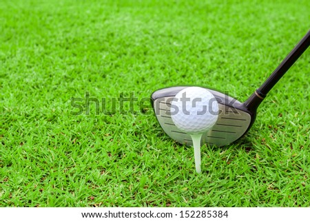 golf tee ball club driver in green grass course preparing to shot - stock photo