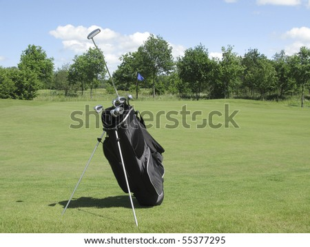 Golfbag with irons and putter sticking out near golf green - stock photo