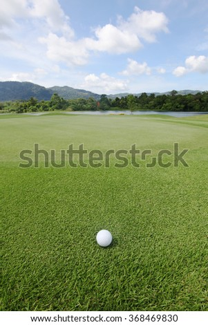 Golfball on grass of golf course at sunny day - stock photo