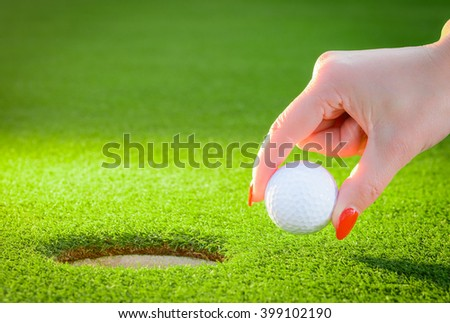 golfball regarded a woman's hand to the hole - stock photo