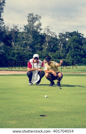 Golfer and caddy, contemplating putting shot. Toned image - stock photo