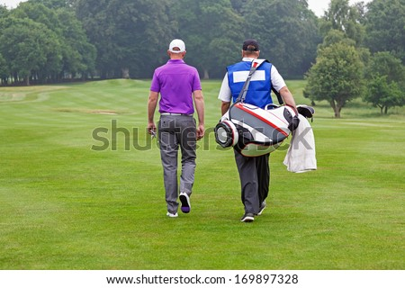 Golfer and caddy walking towards a ball on a par 4 fairway.  - stock photo