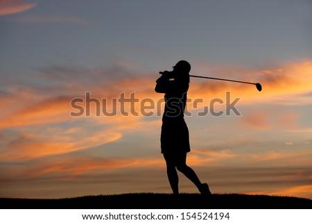 Golfer at sunset. - stock photo