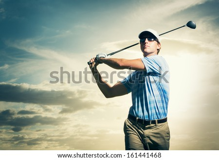 Golfer at sunset, Man swinging golf club with dramatic sunset sky