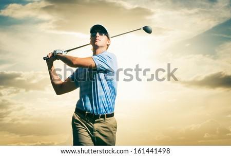 Golfer at sunset, Man swinging golf club with dramatic sunset sky  - stock photo