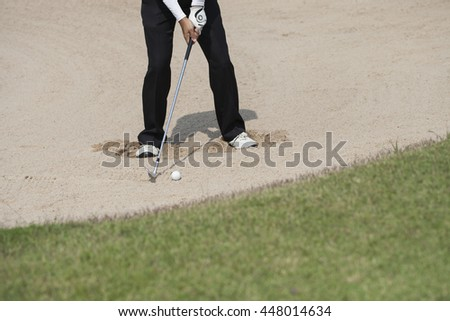 Golfer blasting out of bunker onto green. - stock photo