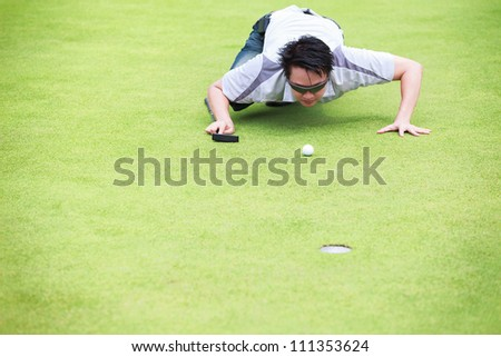 Golfer checking line of putt on green - stock photo