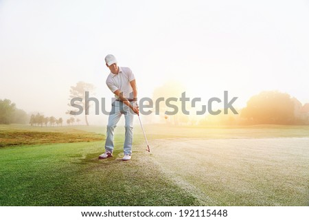 Golfer chipping onto the green at sunrise on the golf course in misty conditions - stock photo