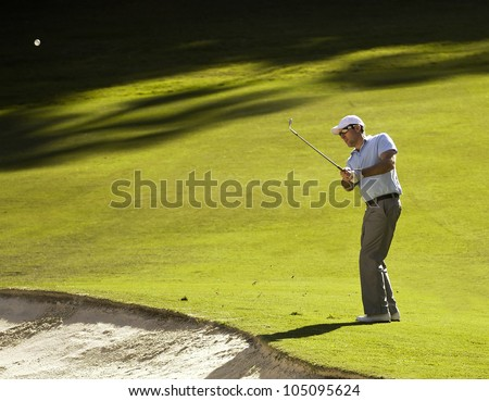 Golfer chips off the fairway - stock photo
