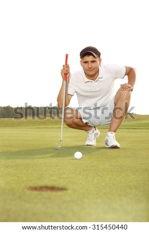 Golfer crouching and eyeing up a putt - stock photo