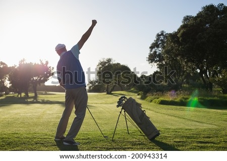 Golfer happy with his shot on a sunny day at the golf course - stock photo