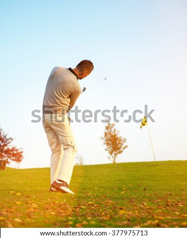 Golfer hits golf course in summer / autumn